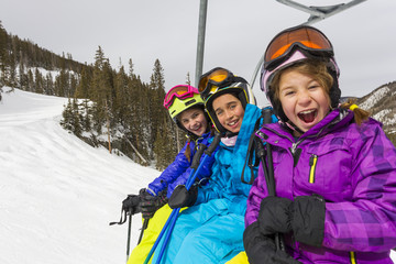 Girls riding ski lift on snowy slope