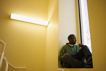 African teenager sitting in window sill