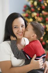 Hispanic boy kissing mother on cheek
