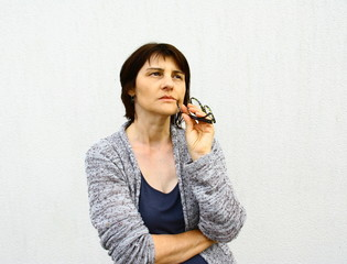 femme 50 ans,pensive,interrogative sur fond blanc