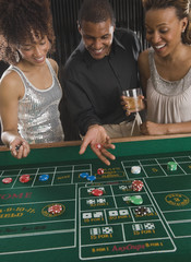 African man and women playing craps at casino