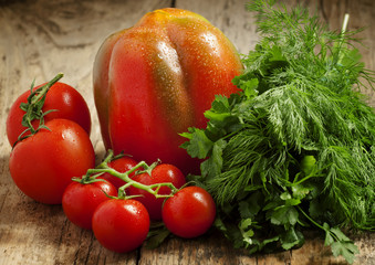 Fresh red tomatoes with parsley and dill on a wooden table