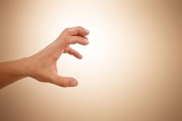 Hand greift nach etwas vor beigen Hintergrund