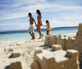 Hispanic family with sand castle in foreground