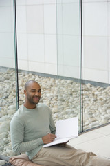 African man writing in notepad