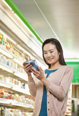 Chinese woman looking at package in store