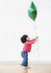 Mixed race girl holding helium balloon