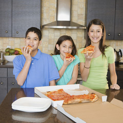 Multi-ethnic siblings eating pizza