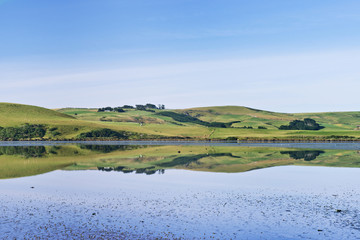 Rural hills reflected in calm estuary