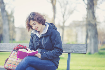 Young girl writing in daily journals at park