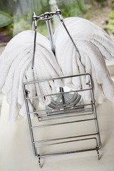 Mounds of white towels and linen folded over a rack