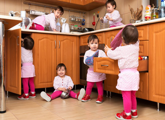 Happy playful girl playing in the kitchen