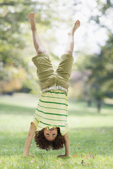 Mixed Race boy performing handstand