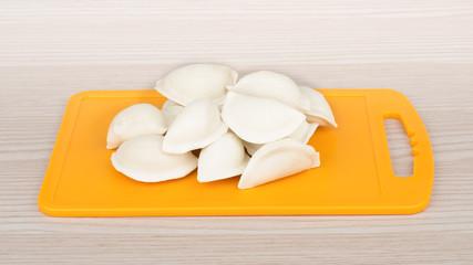 Raw frozen dumplings on board