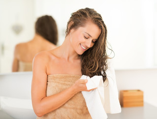 Happy young woman wiping hair with towel in bathroom