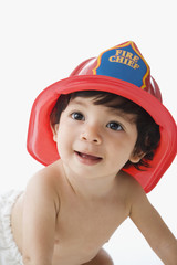 Hispanic baby wearing Fire Chief helmet