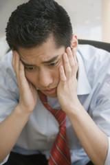 Korean businessman with head in hands looking worried
