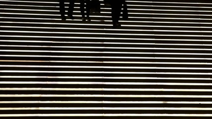 Silhouette of three people coming down a staircase light