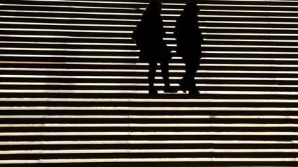 Silhouette of five women in a staircase light.