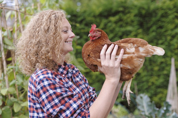 Caucasian farmer smiling with chicken