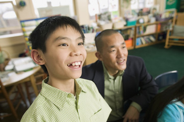 Asian son with father in classroom