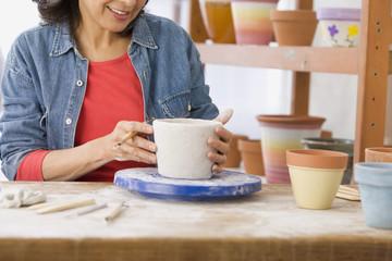 Hispanic woman making pot on potter's wheel