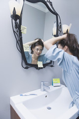 Woman getting ready in front of mirror