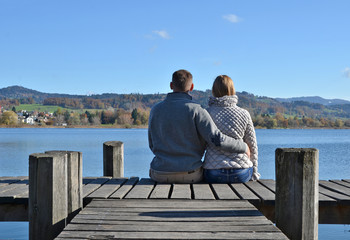 A couple on the wooden jetty at a lake. Switzerland