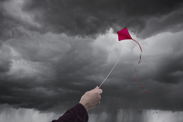 Caucasian man flying kite in storm