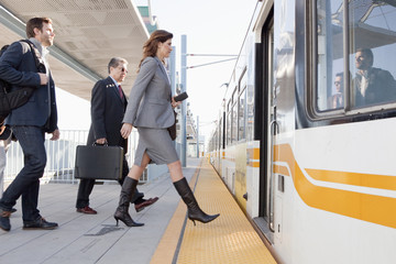 Business people boarding train in station