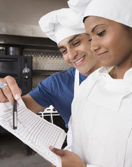 Multi-ethnic pastry chefs looking at paperwork