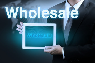 businessman holding tablet  word WHOLESALE on virtual screen.