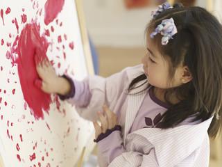 Asian girl finger painting on easel