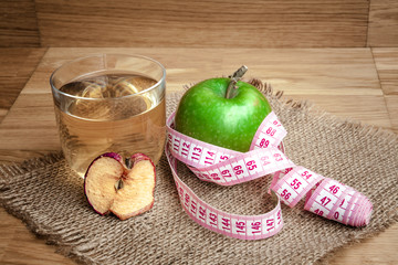 Apple juice with apples on wooden background