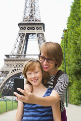 Caucasian mother and daughter taking picture by Eiffel Tower, Paris, France