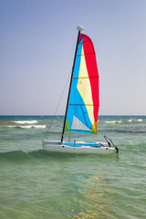 A catamaran in the sea, in shallow water, with the sail up