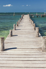 A long wooden jetty or pier, stretching out over the water at Cancun