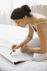 Hispanic woman reading newspaper classifieds