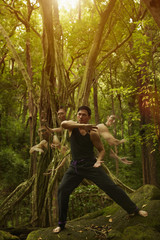 Time lapse view of Asian man practicing yoga in jungle
