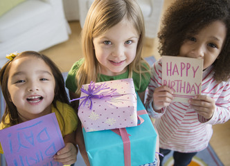 Girls holding presents and cards at birthday party