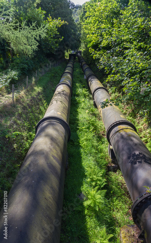 Two large black water pipes, converging in distance. - 82207010