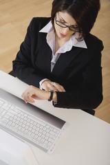 Hispanic businesswoman looking at watch
