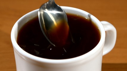 Spoon pouring sugar into a cup of coffee, wood background