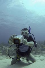 Hispanic scuba diver taking pictures underwater