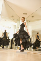 Mixed race woman trying on flamenco dress in shop