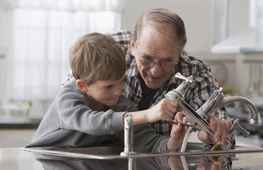 Caucasian man and grandson working on faucet