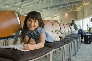 Hispanic girl coloring in airport