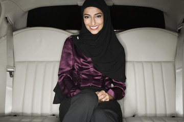 Middle Eastern businesswoman in backseat of limousine