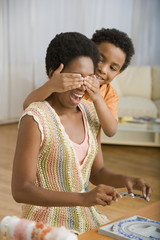 African boy covering mother's eyes
