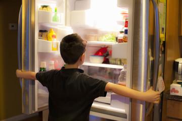 Asian boy searching through refrigerator